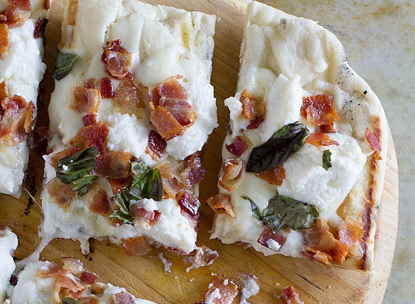 Grilled white pizza with bacon and fresh basil